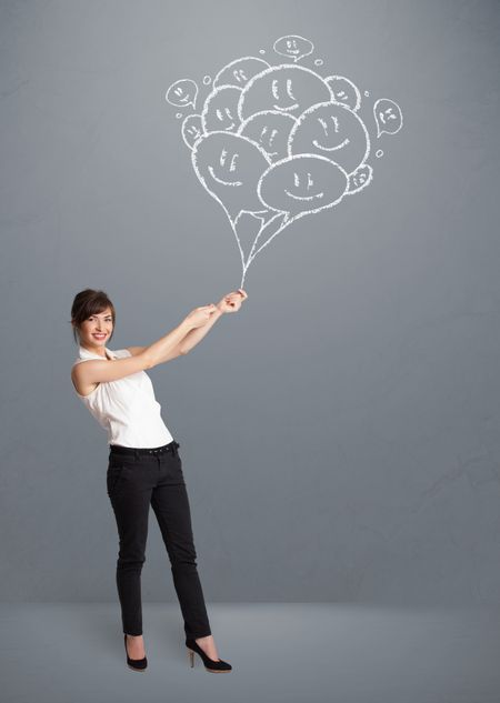 Happy young woman holding smiling balloons drawing