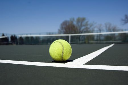 Eye-level view of tennis ball in corner of court