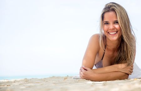 Beautiful woman relaxing at the beach and smiling
