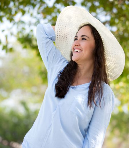 Happy woman in the countryside wearing a hat