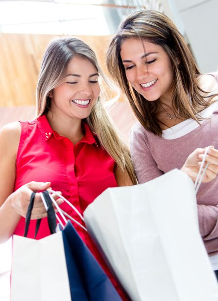 Beautiful shopping women looking at their purchases