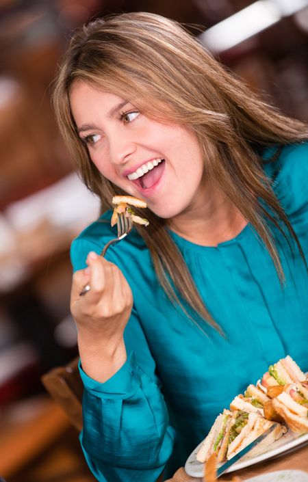 Beautiful happy woman eating at a restaurant