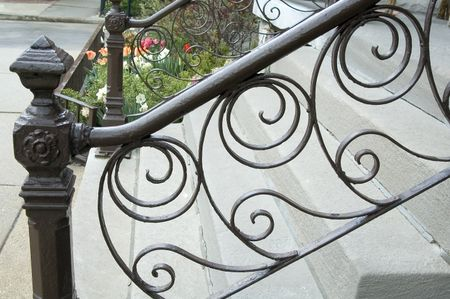 Iron railing with filigree in front of urban walkup
