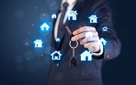 Businessman in suit holding keys with house graphics around and dark background