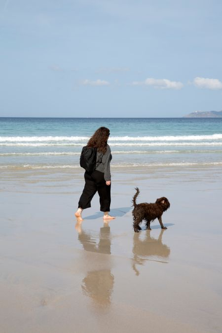 Woman and Dog on Beach in Galicia; Spain