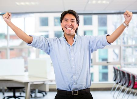 Successful business man with arms up celebrating