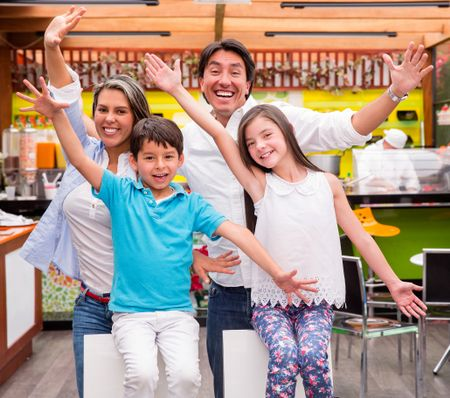 Excited family with arms up at a restaurant