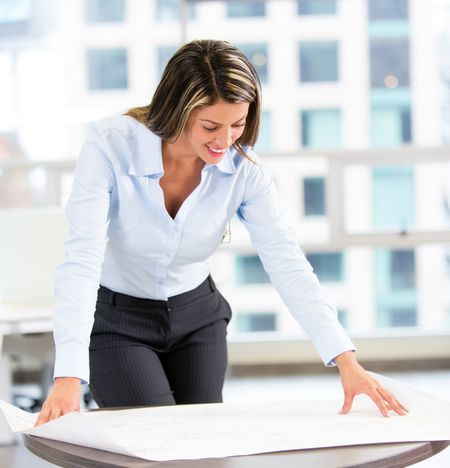 Female architect looking at blueprints at the office