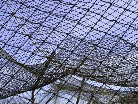 Complexities of practice: Part of netting over batting cage by baseball field on campus of community college