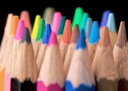 assorted colour pencils close up in perspective with focus on the tips using a shallow depth of field - isolated over a black background