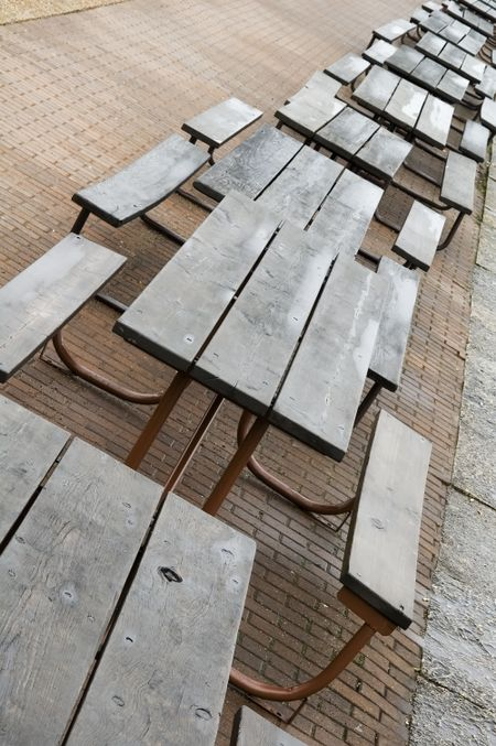Row of wet picnic tables on pavement