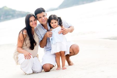 Family smiling at the beach enjoying their vacations
