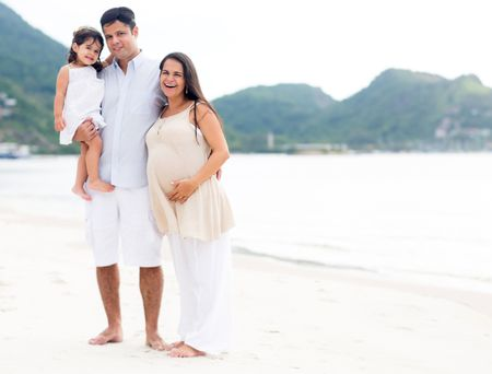 Beautiful family at the beach with pregnant woman
