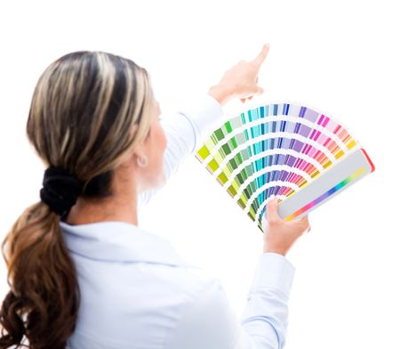 Woman decorating the house and choosing a color for the wall - isolated