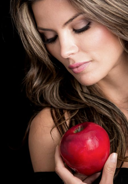 Beauty female portrait holding an apple - isolated over black background