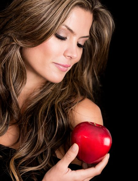Beautiful woman holding the apple of tempation - isolated over black