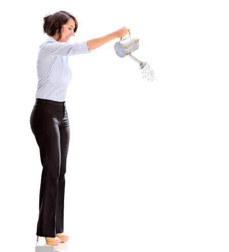 Business woman watering something - isolated over a white background