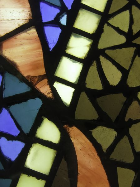 Mosaic effect in closeup of stained glass window with orange, blue, and olive green