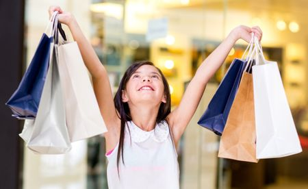 Happy girl holding shopping bags with her arms open