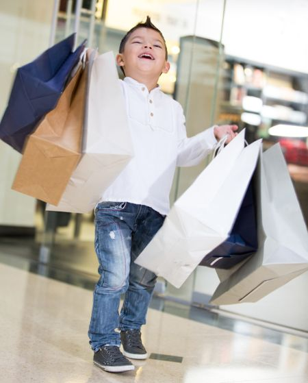 Happy shopping boy holding bags and smiling
