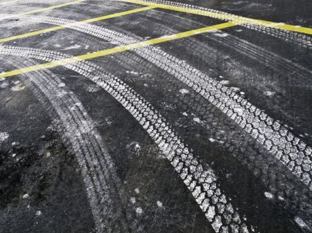 Automotive tire tracks from road salt on asphalt pavement in winter, northern Illinois