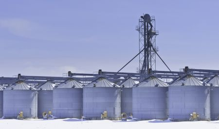 Steel grain silos and control tower above snow in March, central Illinois