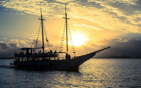 Boat sailing in the sea with a beautiful set sunset behind