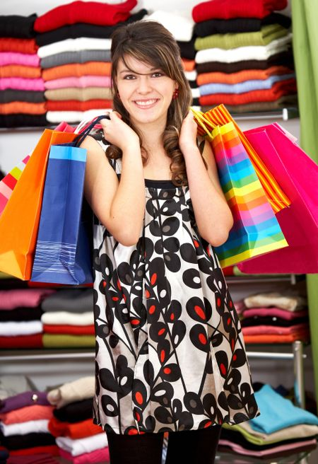 Casual woman with shopping bags in a store smiling