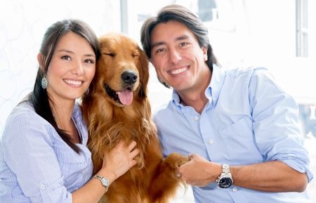 Happy couple holding their dog
