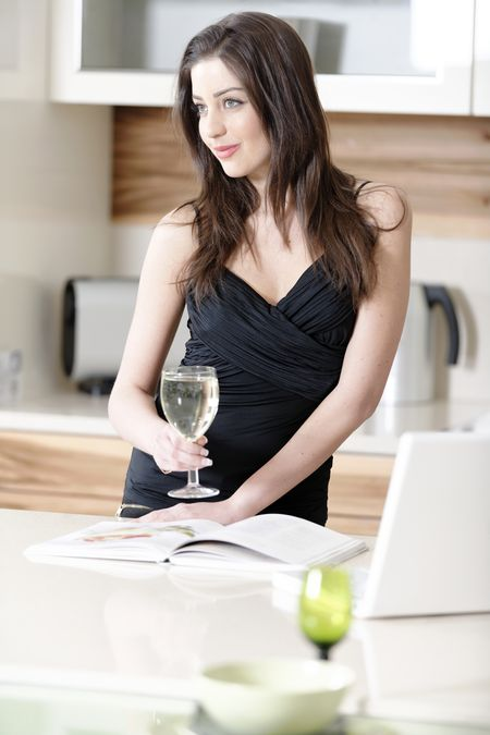 Attractive young woman using a laptop while enjoying a glass of wine in the kitchen