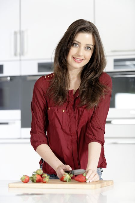 Beautiful young woman preparing strawberries in her white kitchen