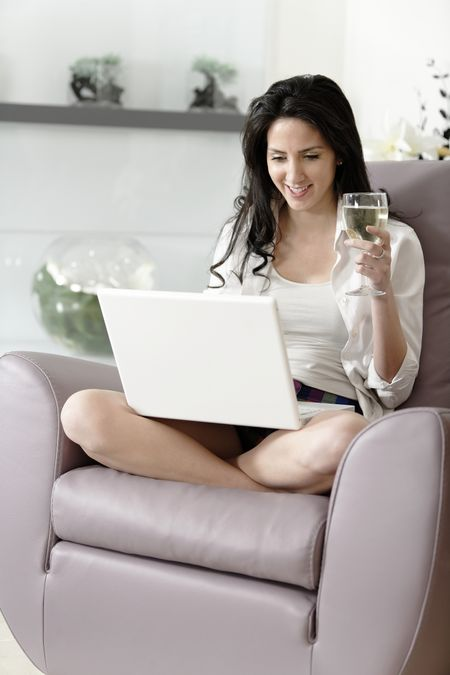 Beautiful young woman enjoying a glass of wine in her elegant living room.
