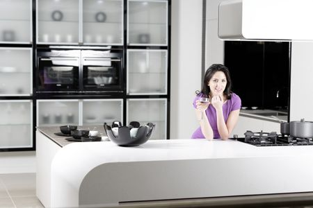 Attractive young woman in a dinner dress holding a glass of wine in her kitchen.