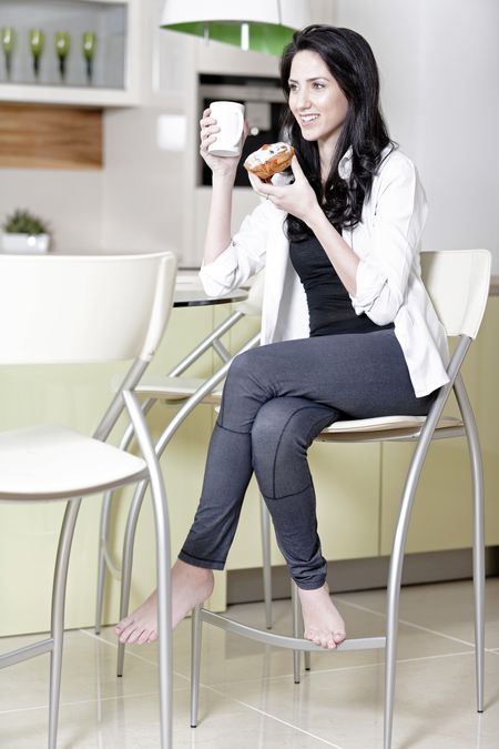Beautiful young woman taking a break in her kitchen with a coffee and cake.