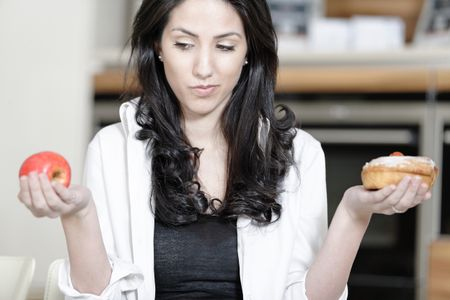 Attractive young woman choosing between a sticky cake or fresh fruit.