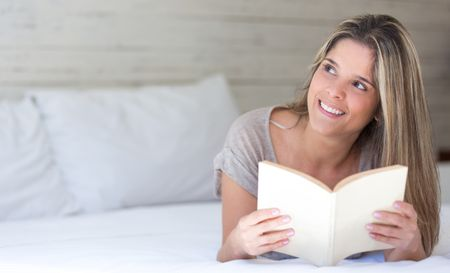 Thoughtful woman enjoying reading a book at home