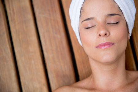 Relaxed woman at the spa enjoying a facial