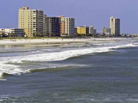 Vacation lifestyle: Surf, sand, and high-rise skyline along shore of Jacksonville Beach, Florida, on a sunny afternoon