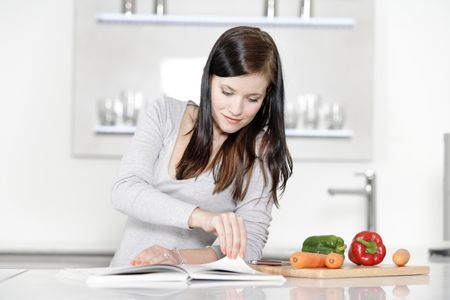 Beautiful young woman reading from a cookery book in her kitchen.