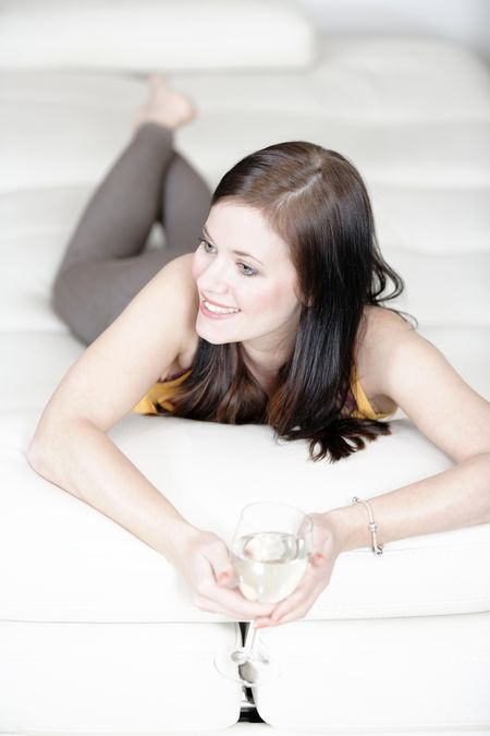 Attractive young woman lying on her sofa enjoying a glass of wine.