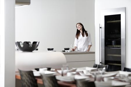 Beautiful young woman relaxing in her elegant white kitchen