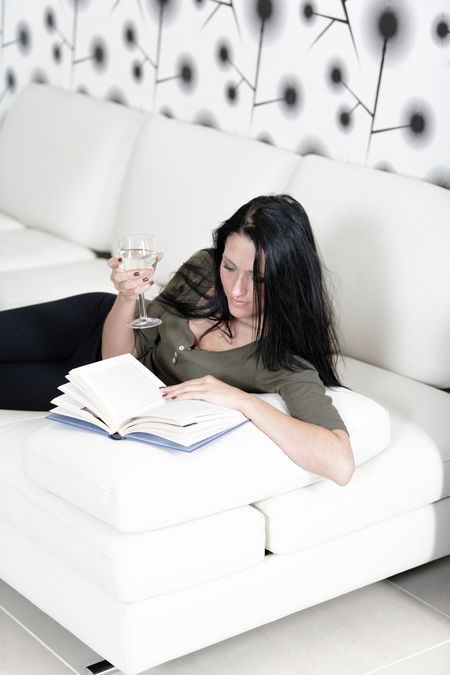 Attractive young woman lying on her sofa enjoying a glass of wine and a good book.
