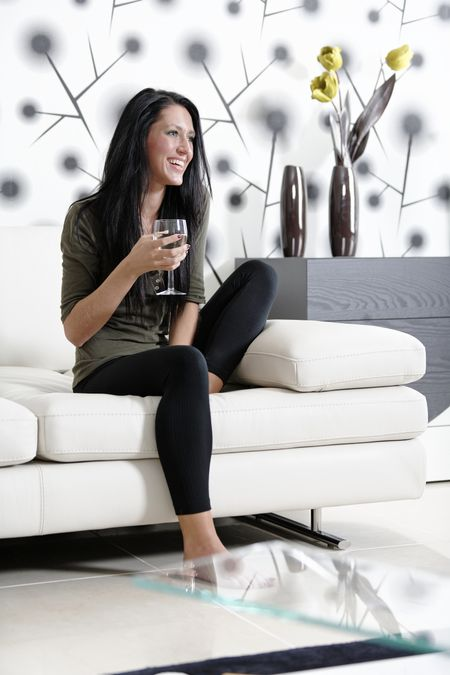 Attractive young woman relaxing on her sofa at home with a glass of white wine.