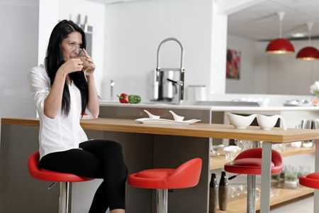 Attractive young woman taking a coffee break in her kitchen