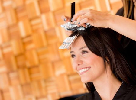 Woman coloring her hair at the beauty salon
