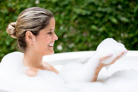 Woman taking a bubble bath in the hot tub