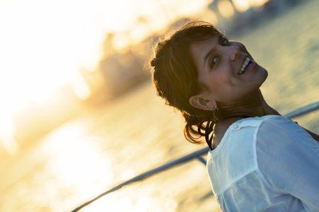 Beautiful woman portrait enjoying the sunset on a boat