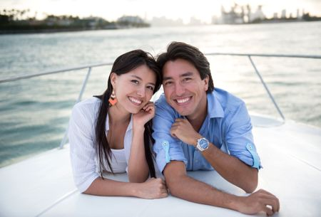 Happy couple in a yacht enjoying sailing and smiling