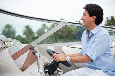Handsome man driving a yacht looking very happy