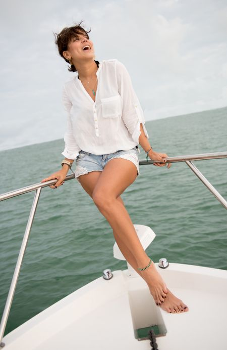 Beautiful summer woman on a yacht posing and looking happy